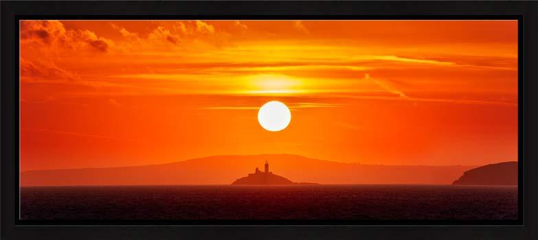 The golden sun rising over Godrevy Lighthouse in St Ives Bay