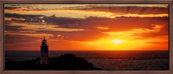 The golden sun beaming across the skies over Godrevy Lighthouse in Cornwall