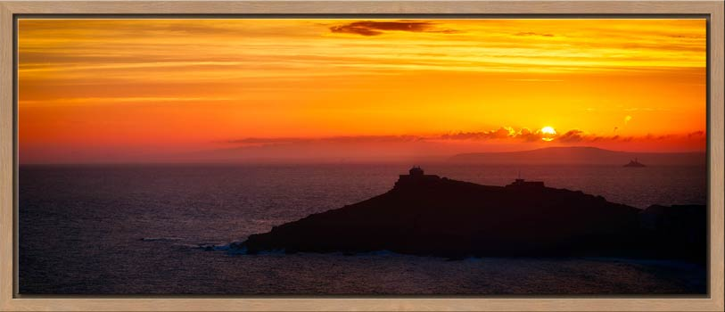 The sun rising over Godrevy Lighthouse and the Island in St Ives, Cornwall