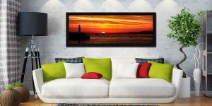 The peeking over the horizon in St Ives Bay in Cornwall. Golden skies above Smeaton's Pier and Godrevy Lighthouse - Black oak floater frame with acrylic glazing on Wall