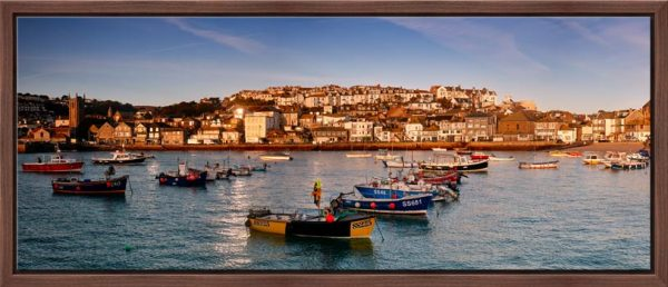 The early morning sunshine warms the boats and buildings of St Ives in Cornwall